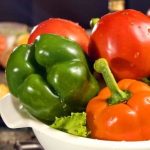 Two orange bell peppers, a green bell pepper, two tomatoes and some lettuce